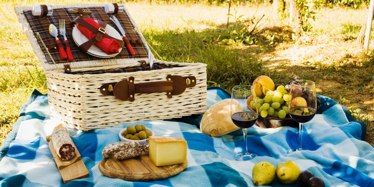 Two glasses of good picnic wine amidst a spread of delicious picnic food